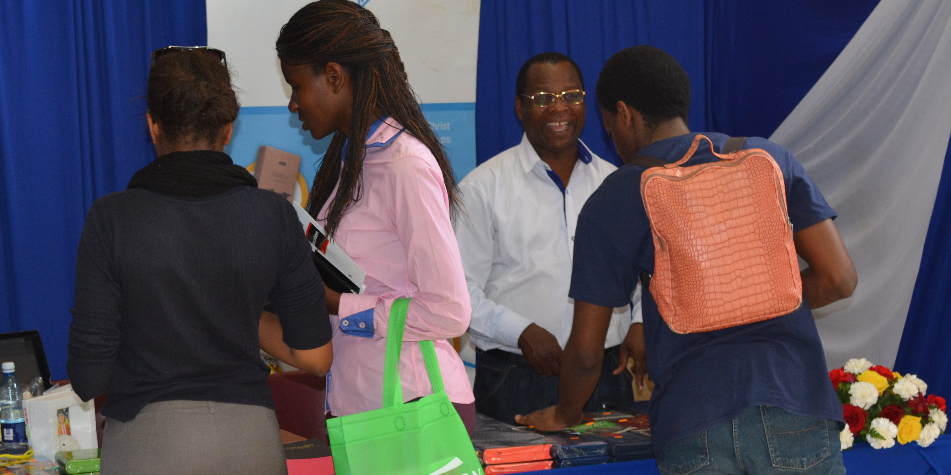 Mr. Charles Wakhaya the Sales Manager Exhibiting bibles to customer at the bible exhibition desk during the 2016 Nairobi International Book Fair